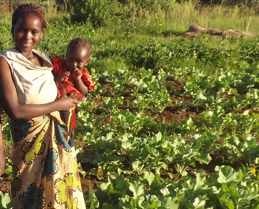 Figure 1. A farmer displays her crop production that has improved through agroecological management; © G. McAllisterA